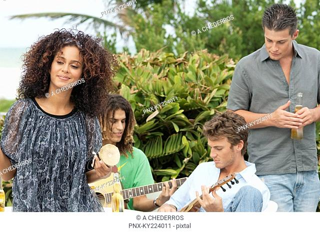 Woman holding a drum with her friends playing guitars