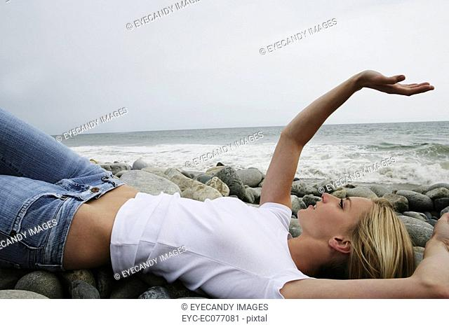 Portrait of young woman lying on rocky beach with arm up