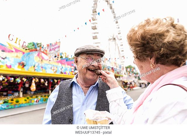 Portrait of happy senior man having fun with his wife on fair