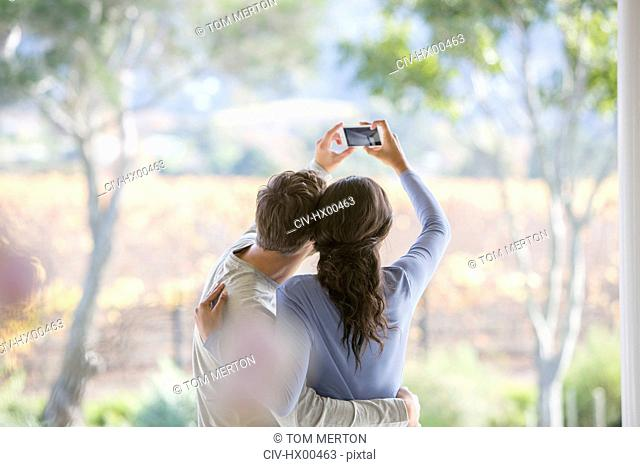 Couple taking selfie with camera phone on patio