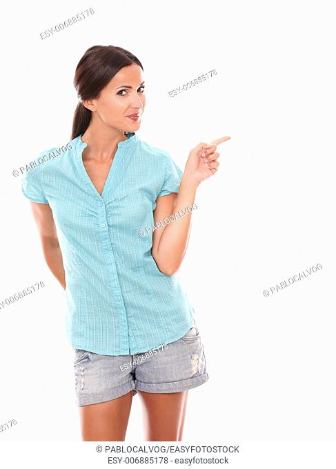 Pretty latin female pointing to her left while smiling and looking at you in white background - copyspace