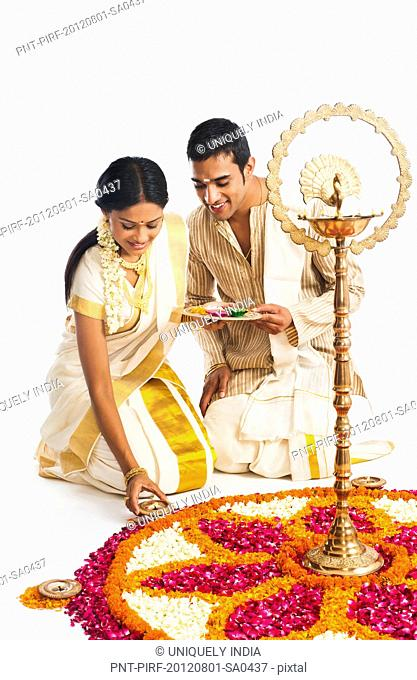South Indian couple making a rangoli of flowers at Onam