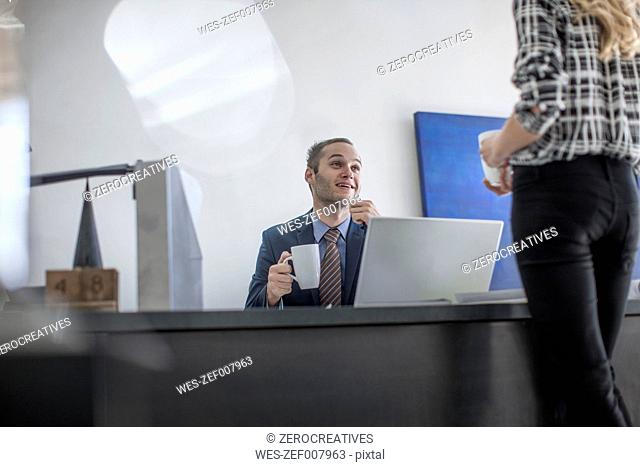 Businessman at desk with cup of coffee looking at colleague