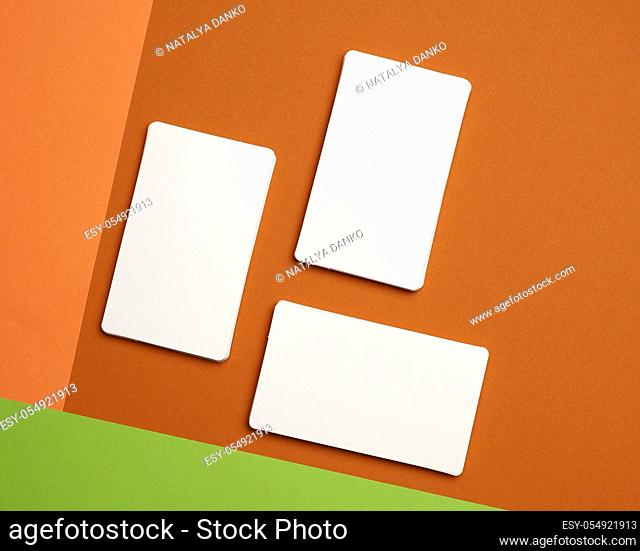 piles of white paper blank business cards on orange-green background, flat lay