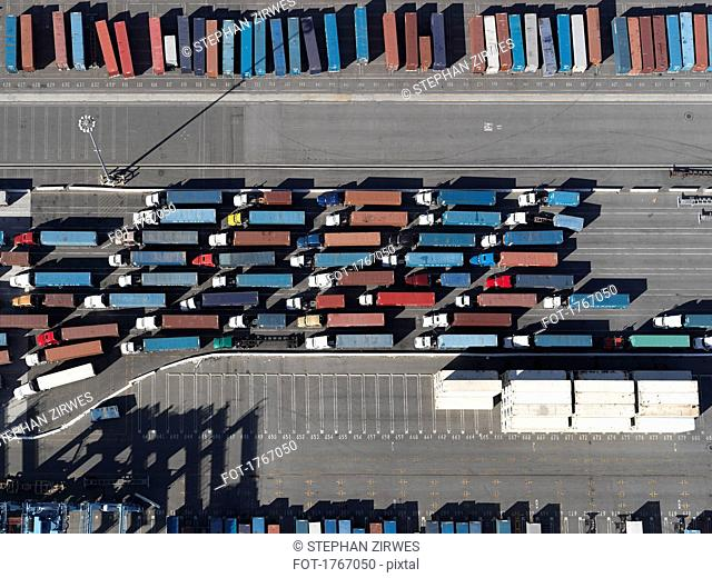 Aerial view semi trucks with containers in sunny shunting yard, Los Angeles, California, USA
