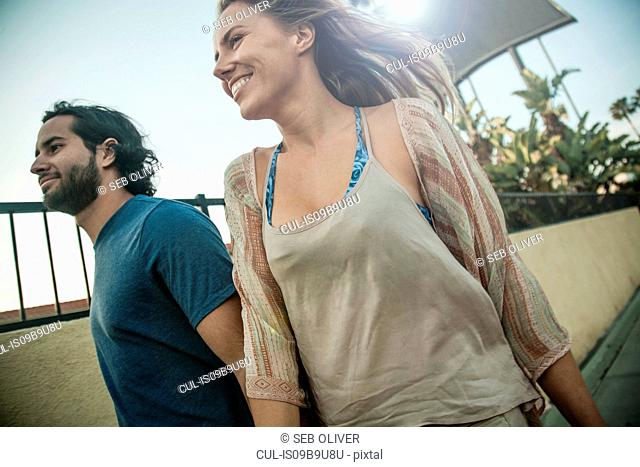 Young couple, walking outdoors, smiling
