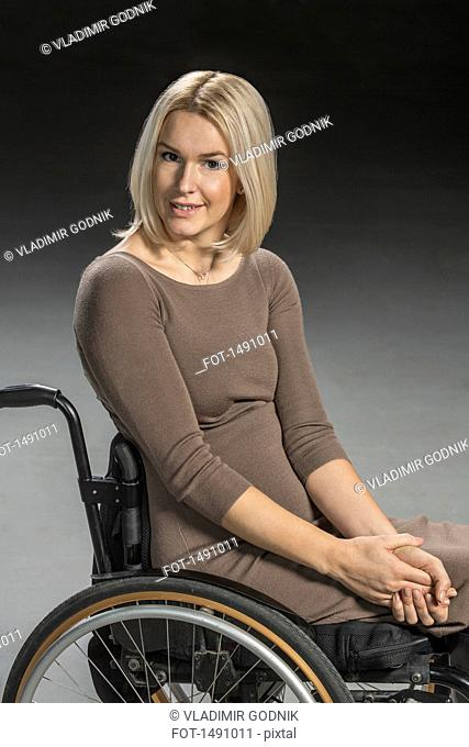 Portrait of confident woman sitting in wheelchair