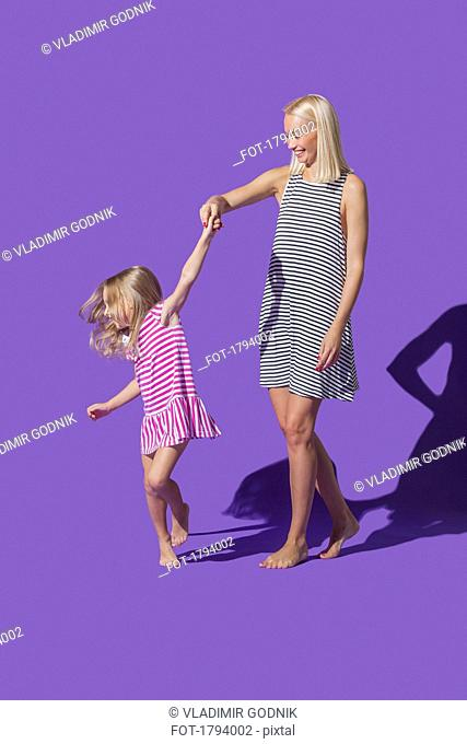 Mother and daughter in striped dresses dancing on purple background