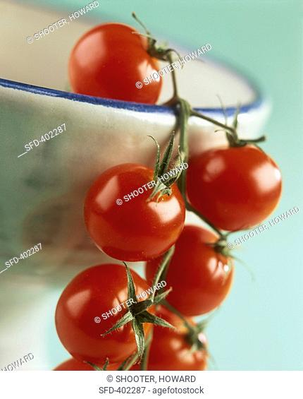 Vine tomatoes hanging over the rim of a bowl
