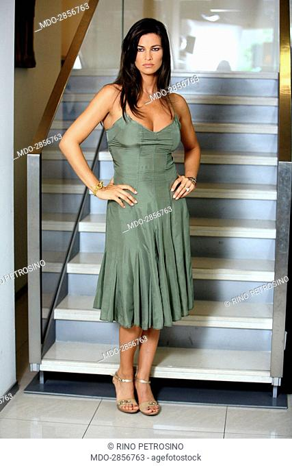 Italian actress Manuela Arcuri posing in a silk dress for a photo shooting beside a staircase. (She wears clothes by Richmond and shoes by Casadei)
