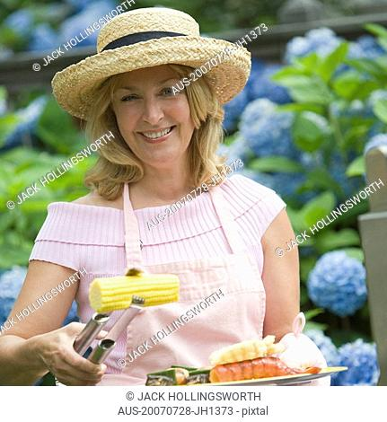 Mature woman preparing food and smiling