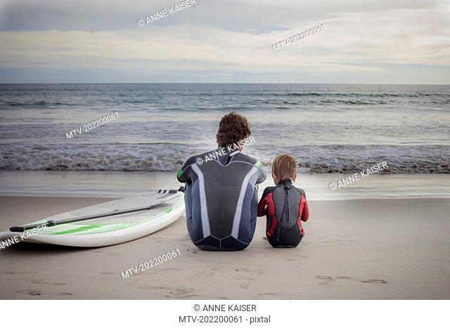 Rear view of father with his son looking at view and sitting on the beach, Viana do Castelo, Norte Region, Portugal