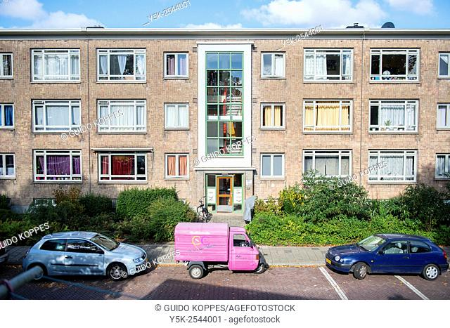 The Hague, Netherlands. Little pink three wheel motorized vehicle, parked in front of 1950's build apartment building