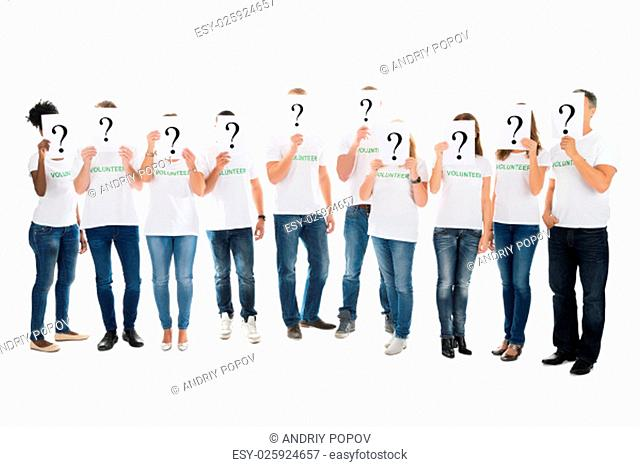 Full length of volunteers covering faces with question mark signs against white background