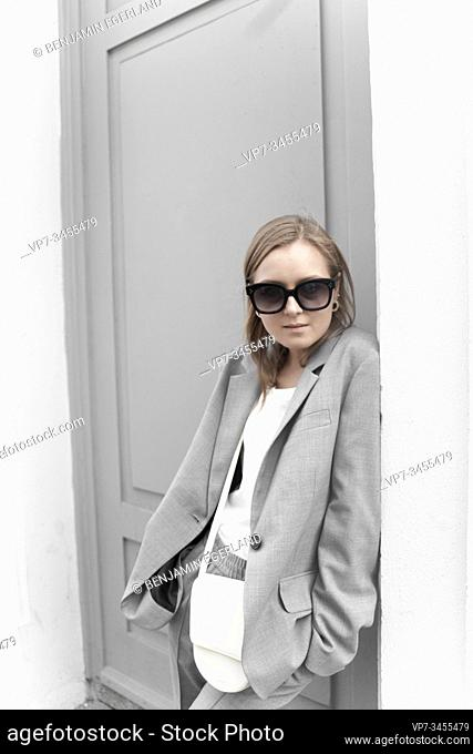 Fashionable woman leaning against grey door. Munich, Germany