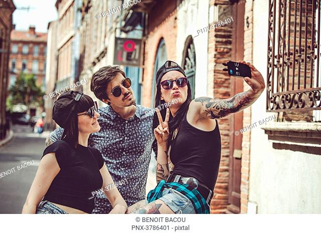 Selfie of three young people in an urban landscape