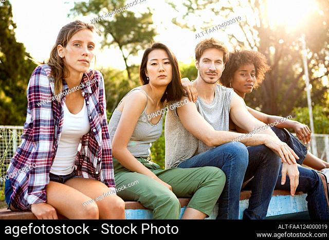 Group of young friends sitting together in park