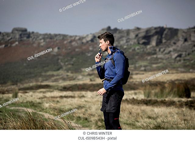 Male runner drinking from tube at Stanage Edge, Peak District, Derbyshire, UK
