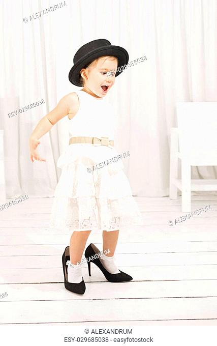 Adorable cute caucasian girl wearing white dress, black hat and black high heel shoes. Little girl trying to walk with big high heel shoes