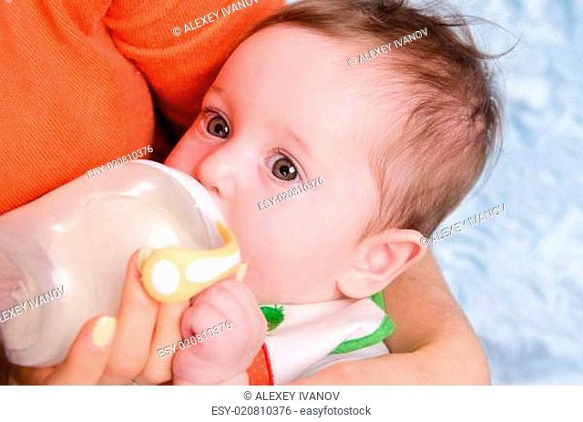 Six month old baby drinking milk from a bottle