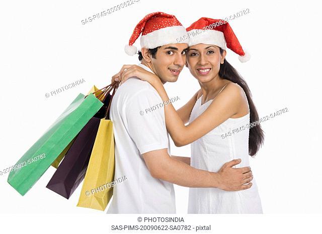 Couple wearing Santa hats and romancing