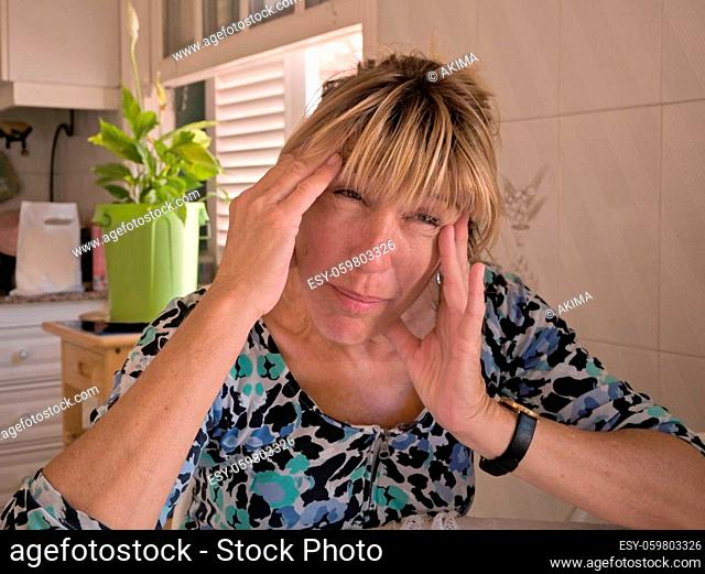 A woman is sitting at a table, her head is held in her hands, her face is consumed with pain. She has a headache, is stressed