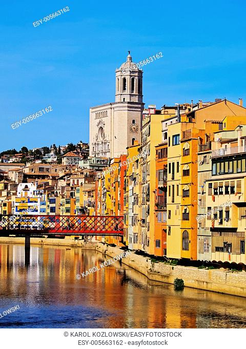 Colorful houses and the cathedral of Girona reflecting in the Onyar River