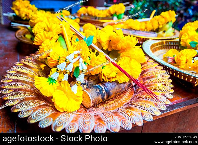Buddhist offerings of flowers, incense, banana and rice on a plate in the temple, close up, Thailand
