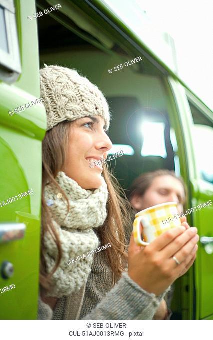 Couple drinking coffee in van