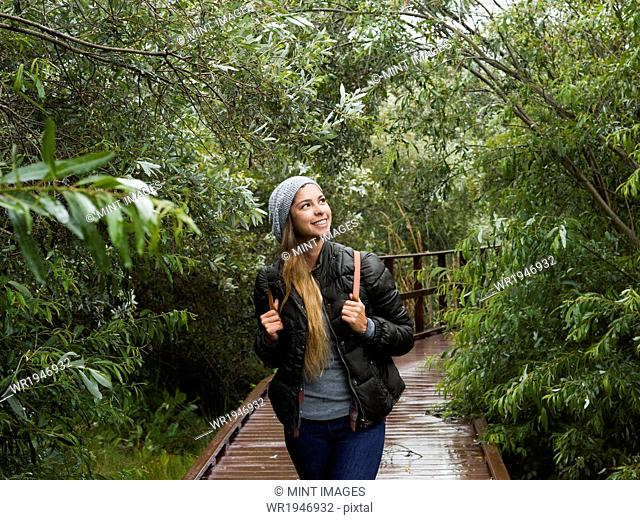 Smiling young woman walking through woodland in a park