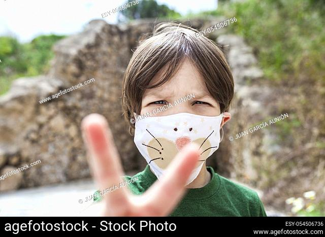 Little boy holds up two fingers for victory over Covid-19 Pandemic. He is wearing face mask with children motifs