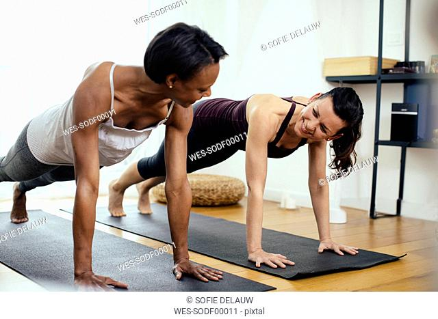 Two women doing gymnastics at home