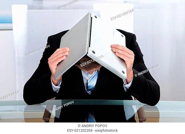Depressed businessman hiding under his laptop