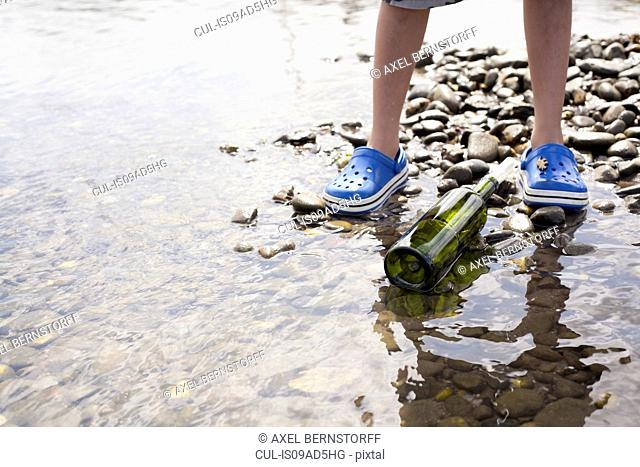 Boy standing by message in a bottle at seaside