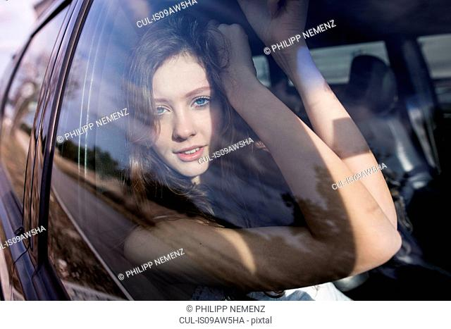 Woman looking out of window in passenger seat of car