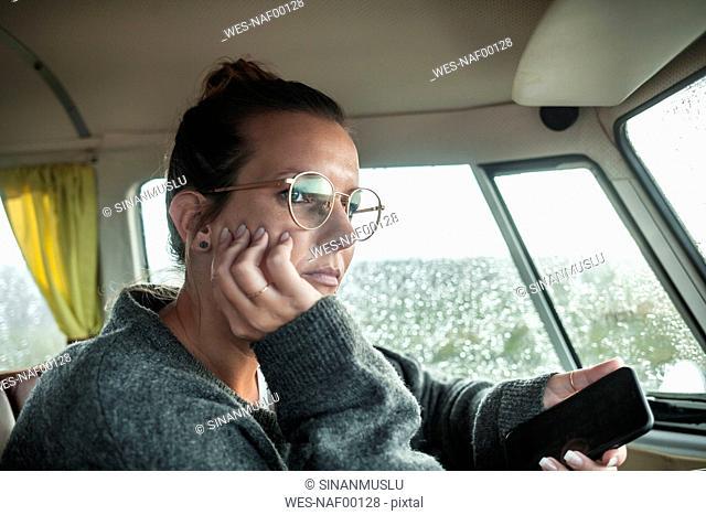 Woman with smartphone in a van looking sideways