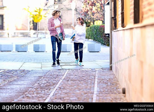 Young man and boy with ice cream and skateboard smiling while walking on footpath