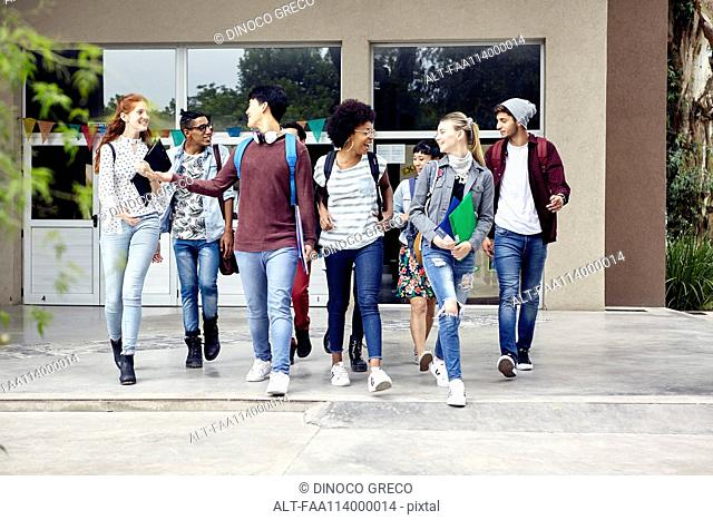 Classmates walking and chatting together on college campus