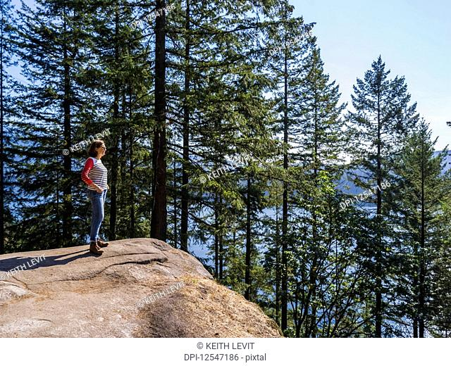 A woman stands at Quarry Rock on the Baden-Powell Trail looking out to the coastline, Deep Cove, North Vancouver; Vancouver, British Columbia, Canada