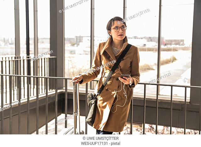 Businesswoman with baggage and cell phone