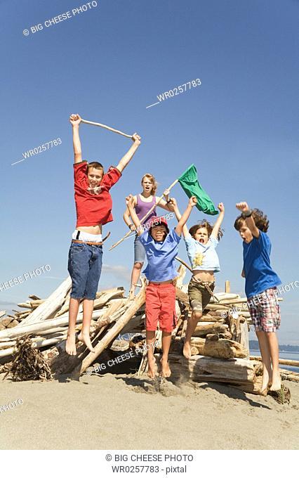 Children jumping next to beach fort