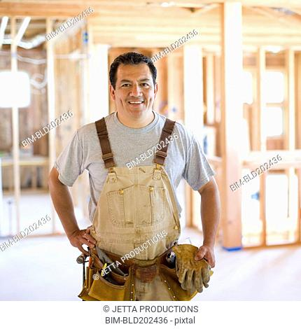 Hispanic construction worker in unfinished room