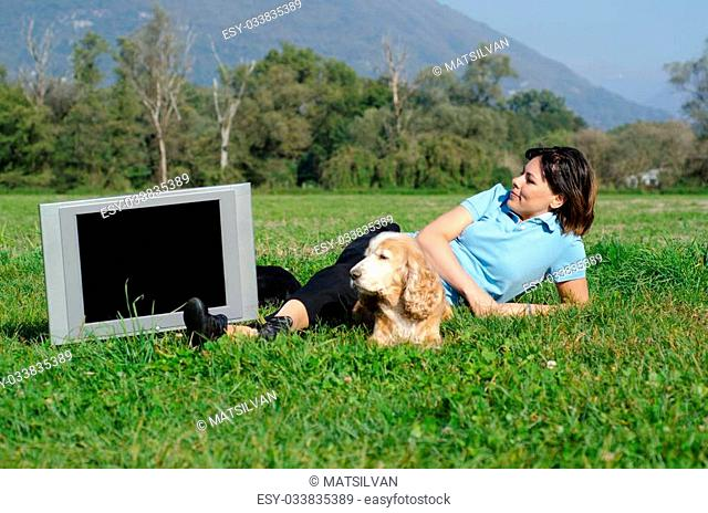 Happy woman lying down and watching the television and she have a dog