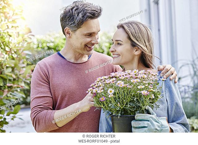 Smiling couple with flowers in front of their home