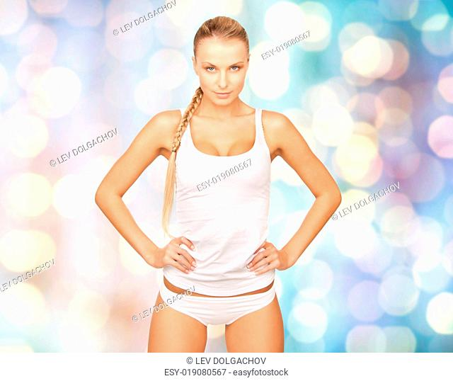 people, beauty, body care and fashion concept - happy beautiful young woman in cotton underwear over blue holidays lights background