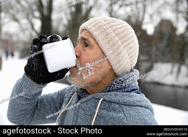 Man drinking tea in mug during winter