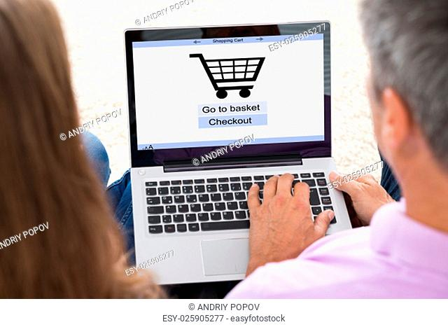 Close-up Of Mature Couple Shopping Online On Laptop