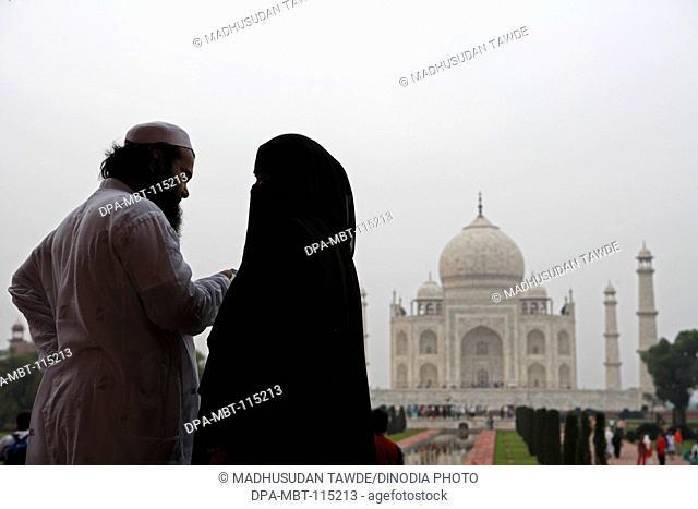 Muslim Couple at Taj Mahal Seventh Wonders of World on the south bank of Yamuna river , Agra , Uttar Pradesh , India UNESCO World Heritage Site
