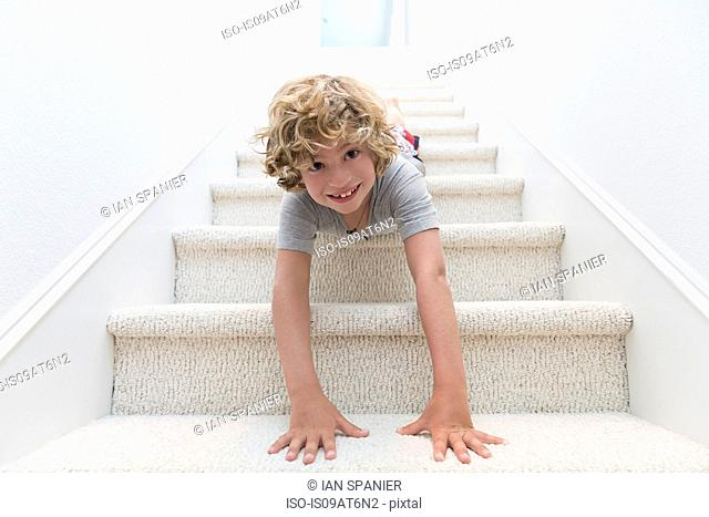 Portrait of boy crawling headfirst down stairs
