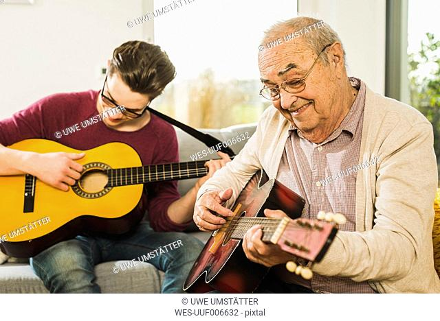 Portrait of senior man playing guitar with his grandson